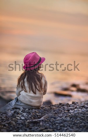Little girl looking on the sea at autumn evening