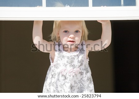 Little Girl Looking Out a Window - stock photo