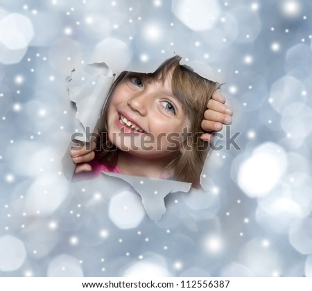 little girl looking out of a hole in a christmas background