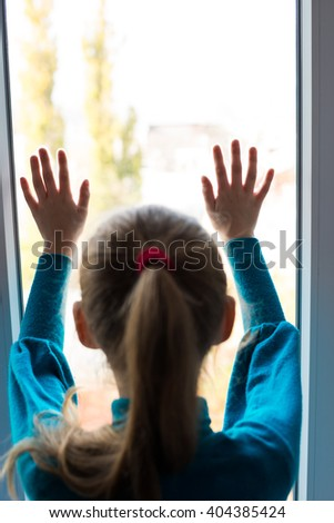 little girl looking out the window - stock photo
