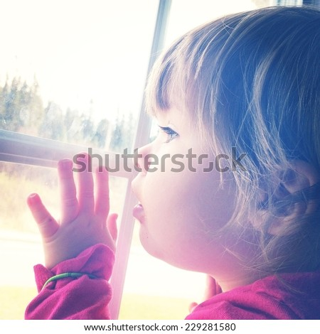 Little girl looking out window with instagram effect - stock photo