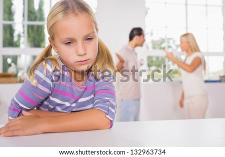 Little girl looking sad in front of fighting parents in the kitchen - stock photo
