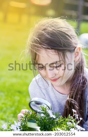Little Girl looking through a magnifying glass  - stock photo