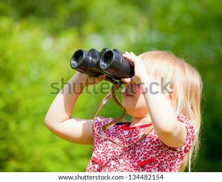 Little girl looking through binoculars outdoor - stock photo