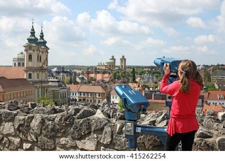 little girl looking through sightseeing binoculars on Eger Hungary - stock photo