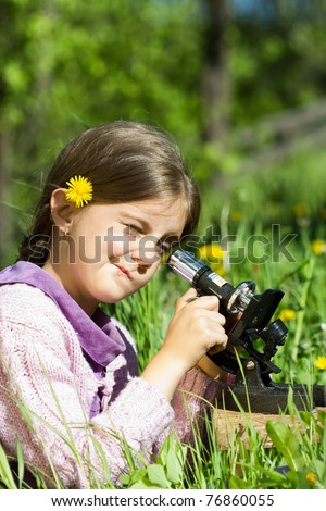 little girl looking with microscope in nature - stock photo