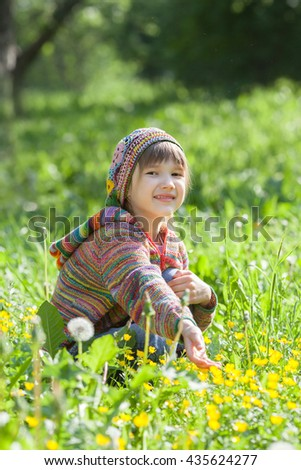 little girl looks at the flowers on a Sunny meadow