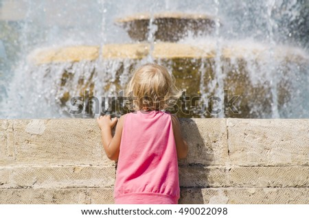 Little girl looks at the fountain. Photographing place: Yessentuki, Stavropol region, Russia
