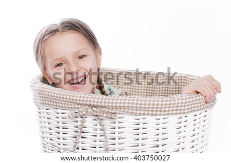 Little girl looks out of a wicker basket with lid. isolated on white background