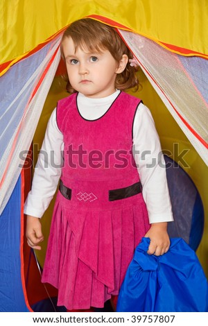 little girl looks out of tourist tent - stock photo
