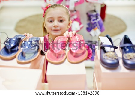 Little girl looks up on toeless shoes that stands on top of shoe boxes - stock photo