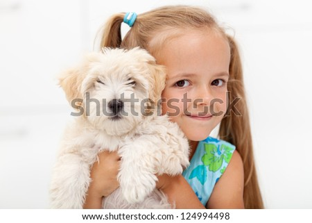 Little girl loves her fluffy dog posing together for the camera - stock photo