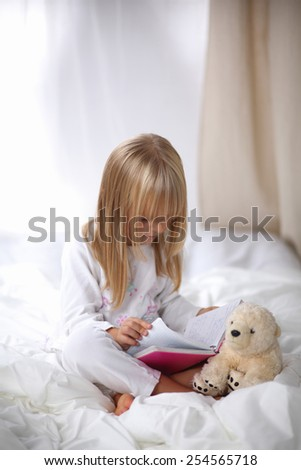 Little girl lying in bed and reading a book .