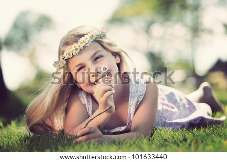 little girl lying in the grass with flowers around her head and smells on a daisy - stock photo