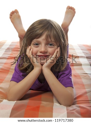 little girl lying on a bed - stock photo