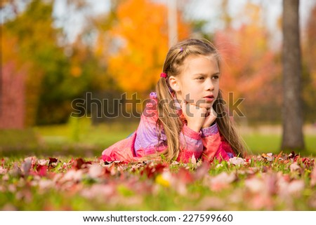 Little girl lying on a colorful leaves in autumn park - stock photo