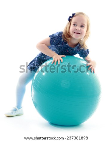 Little girl lying on a large sports ball.Isolated on white background. - stock photo
