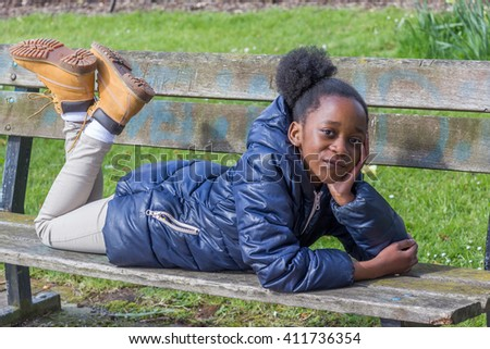 Little girl lying on a park bench with legs up - stock photo