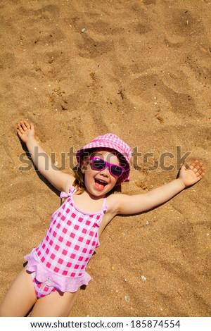 little girl lying on a sandy beach and sunbathe in the sun - stock photo