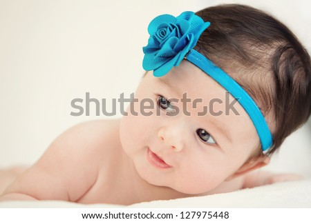 little girl lying on a white cover with blue flower color - stock photo
