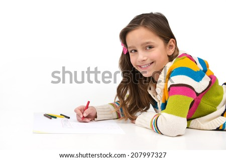 little girl lying on floor and smiling. side view of schoolgirl drawing picture