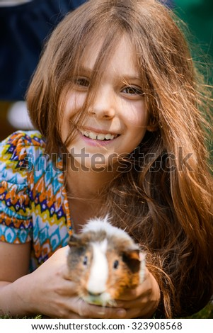 Little girl lying on grass and petting guinea pig. - stock photo