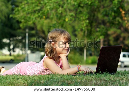 little girl lying on grass with laptop