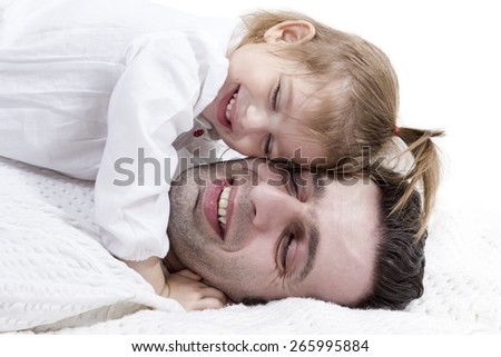 Little girl lying on her father with her eyes closed laughs and hugs him
