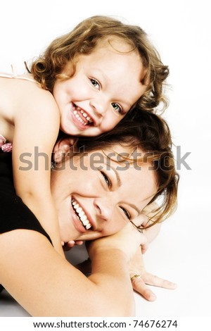 Little girl lying on her mothers back - stock photo