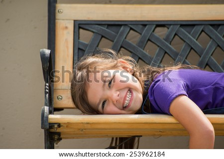 Little girl lying on her stomach on an outside bench with a big smile on her face. - stock photo