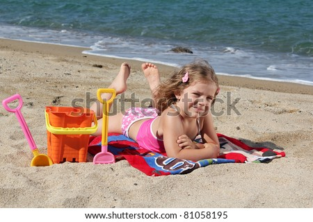 little girl lying on the beach