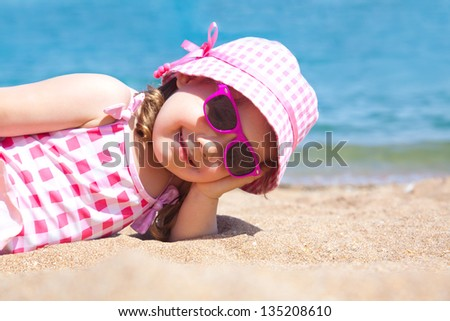 little girl lying on the beach and sunbathe in the sun - stock photo
