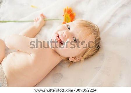 little girl lying on the bed and plaing whith flower - stock photo