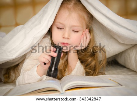 little girl lying on the bed and reading a book