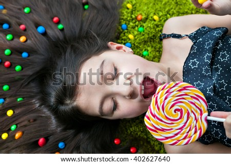 Little girl lying on the floor with his eyes closed and eating candy - stock photo