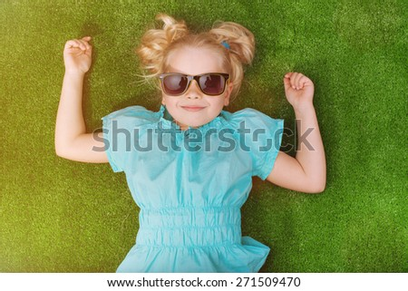 Little girl lying on the grass and dreaming. Beautiful girl in glasses looking at the camera. Sunny summer season. Baby pictures - stock photo
