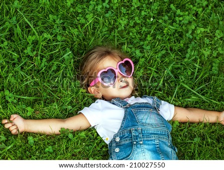 little girl lying on the grass in pink sunglasses, fashion style - stock photo