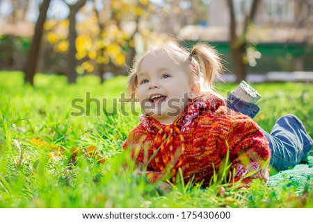little girl lying on the grass in the park