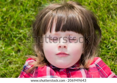 little girl lying on the grass with eyes closed