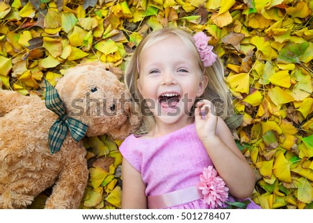little girl lying on the street on the fallen leaves with his friend a teddy bear
