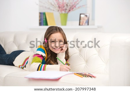 little girl lying on white sofa. small kid writing in notebook and smiling