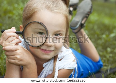 little girl lying with a magnifying glass on a grass - stock photo