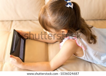 Little girl lying with a tablet on a leather sofa . e-lerning