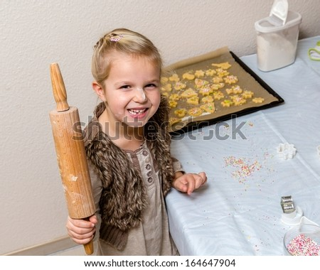 Little girl make cookies at the advent time. Funny child with with flour on the face - stock photo