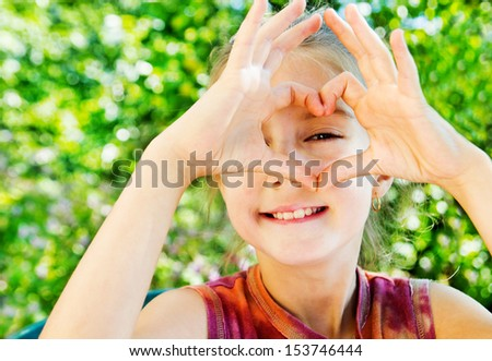 little girl makes a gesture in the form of the heart - stock photo
