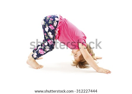 Little girl makes gymnastic exercise. Isolated on white background - stock photo