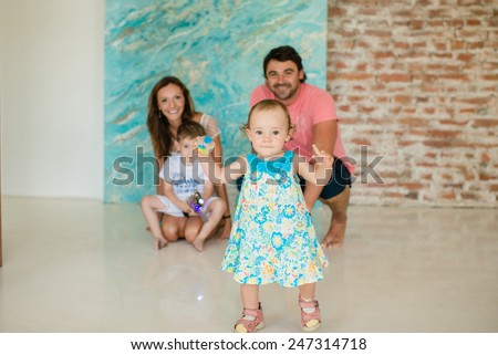 little girl makes the first steps , in the background of her family - stock photo
