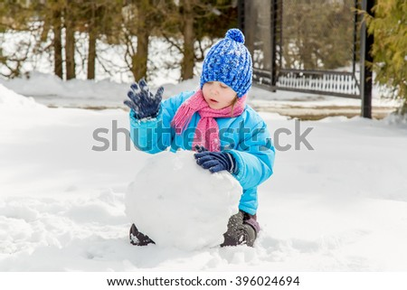 Little girl making a big snowball to build a snowman in winter day