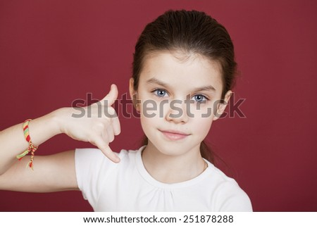 Little Girl making a call me gesture, against background of burgundy wall - stock photo