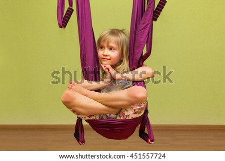 Little girl making aerial yoga exercises, indoor - stock photo